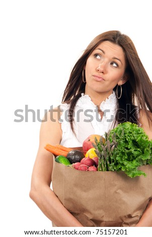 Happy young woman holding a shopping bag full of vegetarian groceries, mango, salad, asparagus, radish, avocado, lemon, carrots, oranges and thinking  isolated on white background