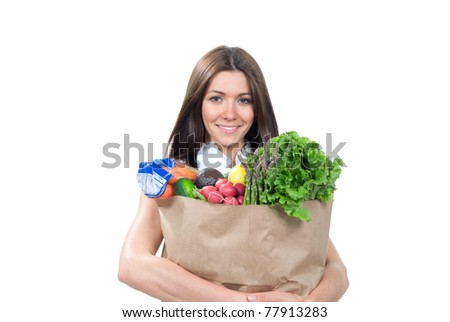 Happy young woman holding a supermarket shopping bag full of groceries, cucumbers, salad, asparagus, radish, avocado, lemon, carrots on white background