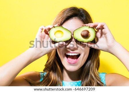 Happy young woman holding avocado halves on a yellow background