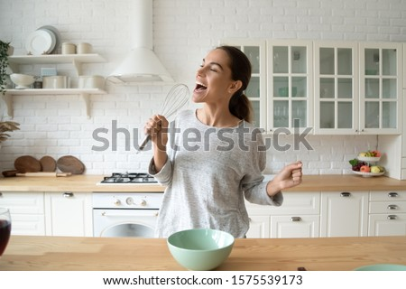 Happy young woman holding beater microphone singing song dancing cooking alone in modern kitchen, funny lady housewife having fun listening music prepare healthy morning meal doing housework at home
