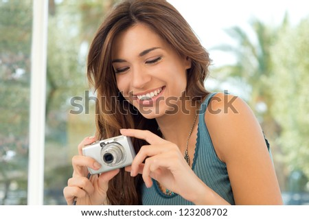 Happy Young Woman Holding Digital Camera And Taking Pictures