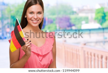 Happy Young Woman Holding German Flag against a street background