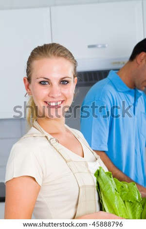 happy young woman holding green vegetables in kitchen, background is her husband chopping veggies