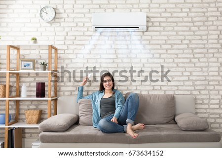 Happy Young Woman Holding Remote Control Relaxing Under The Air Conditioner