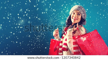 Happy young woman holding shopping bags in a snowy night