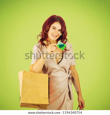 Happy young woman holding shopping bags show a discount card for sale season isolated over green background.