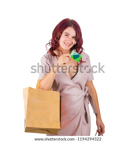 Happy young woman holding shopping bags show a discount card for sale season isolated over white background.