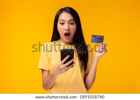 Happy young woman holding smart phone and showing credit card with surprise face Girl stand over yellow background, Online payment, hands holding credit card and using mobile phone for online shopping
