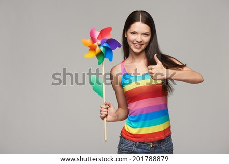 Happy young woman holding toy multicolored pinwheel windmill and gesturing thumb up, over gray background