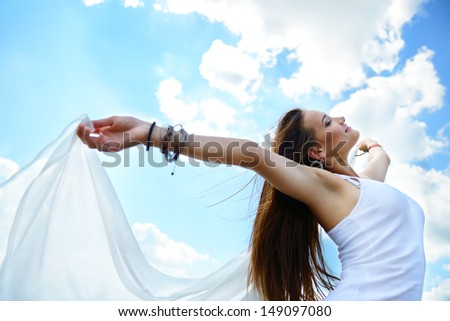 Happy young woman holding white scarf with opened arms expressing freedom, outdoor shot against blue sky