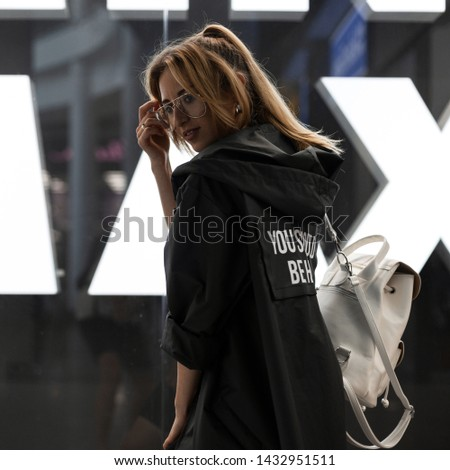 Happy young woman in a fashionable raincoat with hood in stylish glasses with a stylish vintage backpack is standing near a modern glass wall in a shopping center. Joyful urban girl fashion model.