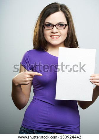 Happy young woman in a lilac shirt and glasses. Woman holds a poster in her left hand. The right hand points to the poster. On a gray background