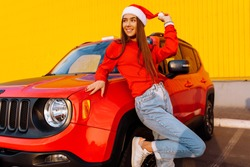 happy young woman in a red sweater and Santa Claus hat posing near a red car on a background of a yellow wall in the city