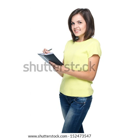Happy young woman in a yellow shirt. Writing in a notebook. Isolated on white background