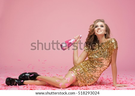 Happy young woman in an evening dress celebrating on a pink background.