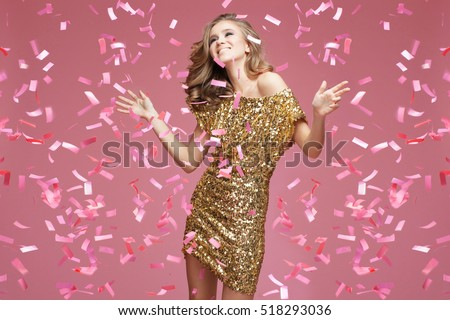 Shutterstock Happy young woman in an evening dress celebrating on a pink background.