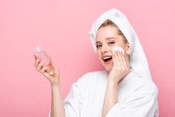 happy young woman in bathrobe with towel on head cleansing face with micellar water and cotton pad isolated on pink