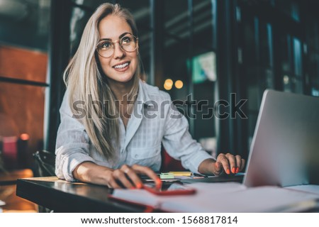 Happy young woman in casual outfit and glasses smiling and looking away while browsing modern laptop and smartphone in cozy restaurant