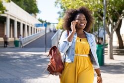 Happy young woman in casual walking while talking over phone. Cheerful african american girl with curly hair using smartphone. Black curvy woman talking on phone outdoor.