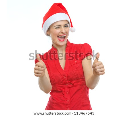 Happy young woman in Christmas hat winking and showing thumbs up