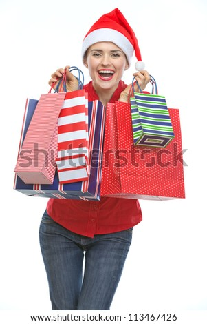 Happy young woman in Christmas hat with shopping bags
