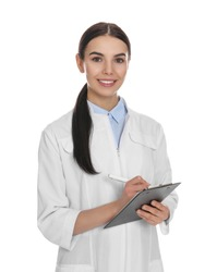 Happy young woman in lab coat with clipboard on white background