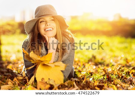 Happy young woman in park on sunny autumn day. Cheerful beautiful girl in gray sweater and floppy hat outdoors on beautiful fall day. Retouched, vibrant colors, back lit, natural light.