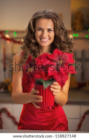 Happy young woman in red dress holding christmas rose in christmas decorated kitchen