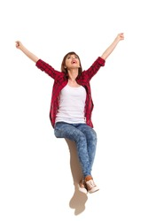 Happy young woman in red lumberjack shirt, jeans and brown sneakers sitting on a top with arms outstretched, shouting and looking up. Full length studio shot isolated on white.