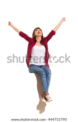 Happy young woman in red lumberjack shirt, jeans and brown sneakers sitting on a top with arms outstretched, shouting and looking up. Full length studio shot isolated on white. #444753790