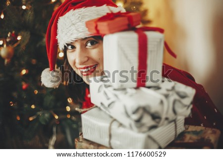 happy young woman in santa hat holding pile of gift boxes at golden beautiful christmas tree with lights in festive room. happy winter holiday atmospheric  moments