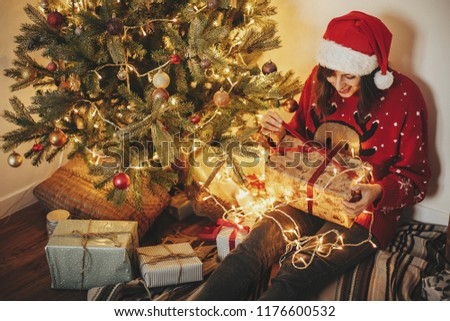 happy young woman in santa hat opening gift box at golden beautiful christmas tree with lights and presents in festive room. happy winter holiday atmospheric  moments. seasons greetings