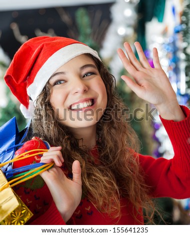 Happy young woman in Santa hat waving while carrying shopping bags at Christmas store