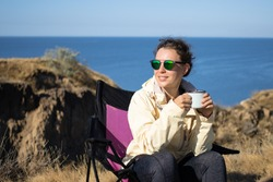 Happy young woman in sunglasses sitting on camping chair and holding iron mug cup of coffee, spending autumn vacation on cliff by blue sea, enjoying calm and peaceful holidays in nature landscape