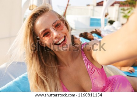 Happy young woman in swimsuit, sunglasses taking a selfie while spending good time a swimming pool resort