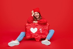 Happy young woman in trendy bright outfit smiling and looking at camera while leaning on speech cloud with like, while symbolizing social media addiction against red background