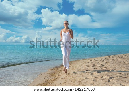 Happy young woman in white clothes running on the beach