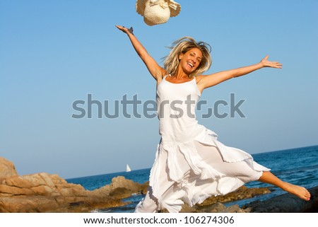Happy young woman in white dress jumping on beach.
