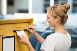 Happy young woman inserting letter in mailbox