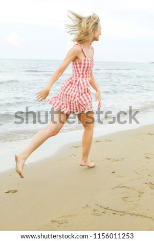 happy young woman is running along seashore, wearing short red checked dress