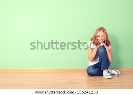 happy young woman is sitting in a room with a blank wall
