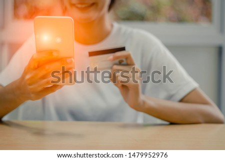 Happy young woman is using smartphone and using Credit Card for Payment #1479952976