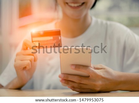 Happy young woman is using smartphone and using Credit Card for Payment #1479953075