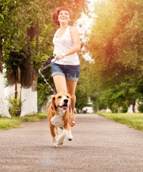 Happy young woman jogging with her beagle dog