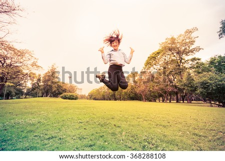 Happy young woman jumping high on the park #368288108