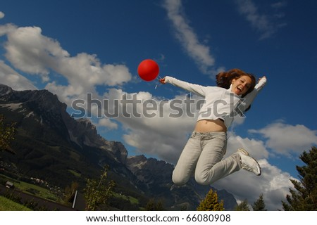 Happy young woman jumping in front of the Austrian Alpen