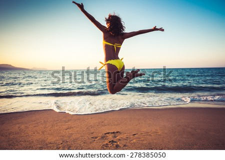 Happy young woman jumping on the beach. Summer vacation and freedom concept #278385050
