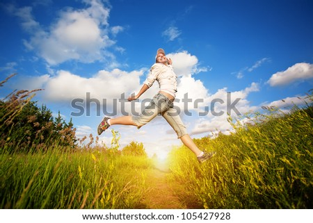 happy young woman jumping over the blue sky