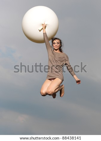 happy, young woman jumping with big, white balloon