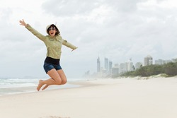 happy young woman jumps on the beach with joyful scream